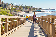 Woman Walking Her Dog Across the Pedestrian Bridge on the San Clemente Beach Trail