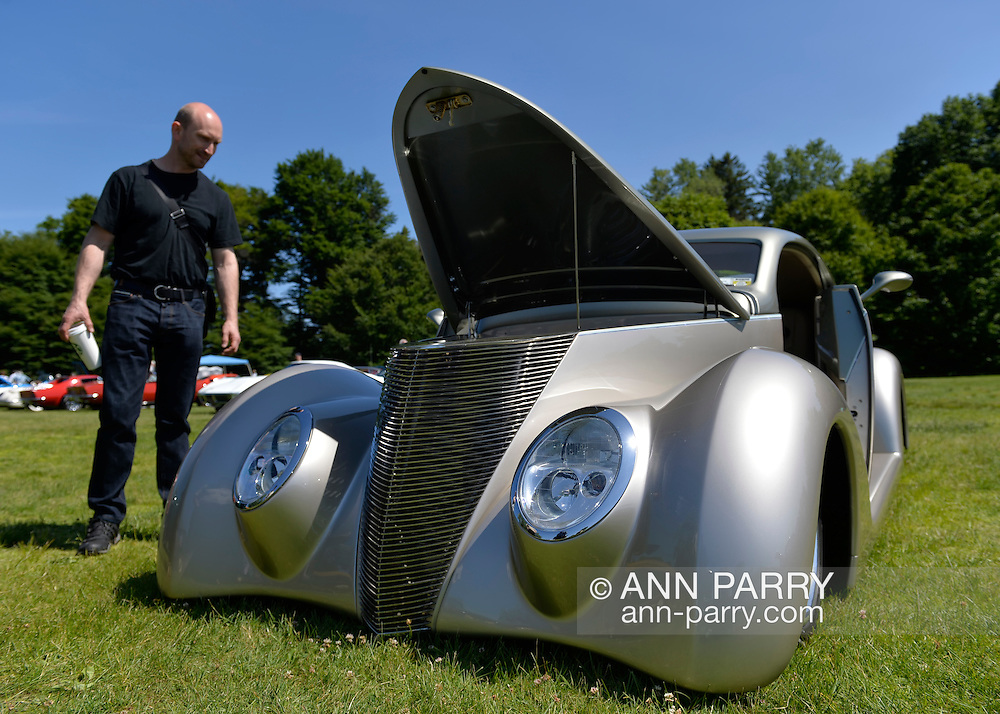 Old Westbury, New York, United States. 7th June 2015. A visitor looks at an ultra low to the ground silver 1937 Ford, the First Place winner in the Modified Car category, at the 50th Annual Spring Meet Car Show sponsored by Greater New York Region Antique Automobile Club of America. Over 1,000 antique, classic, and custom cars participated at the popular Long Island vintage car show held at historic Old Westbury Gardens.