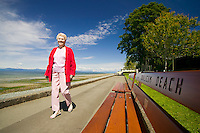 Senior citizens regularly walk the seawalk on Qualicum Beach's waterfront for exercise and to sit and enjoy the beautiful scenery.  Qualicum Beach, Vancouver Island, British Columbia, Canada.