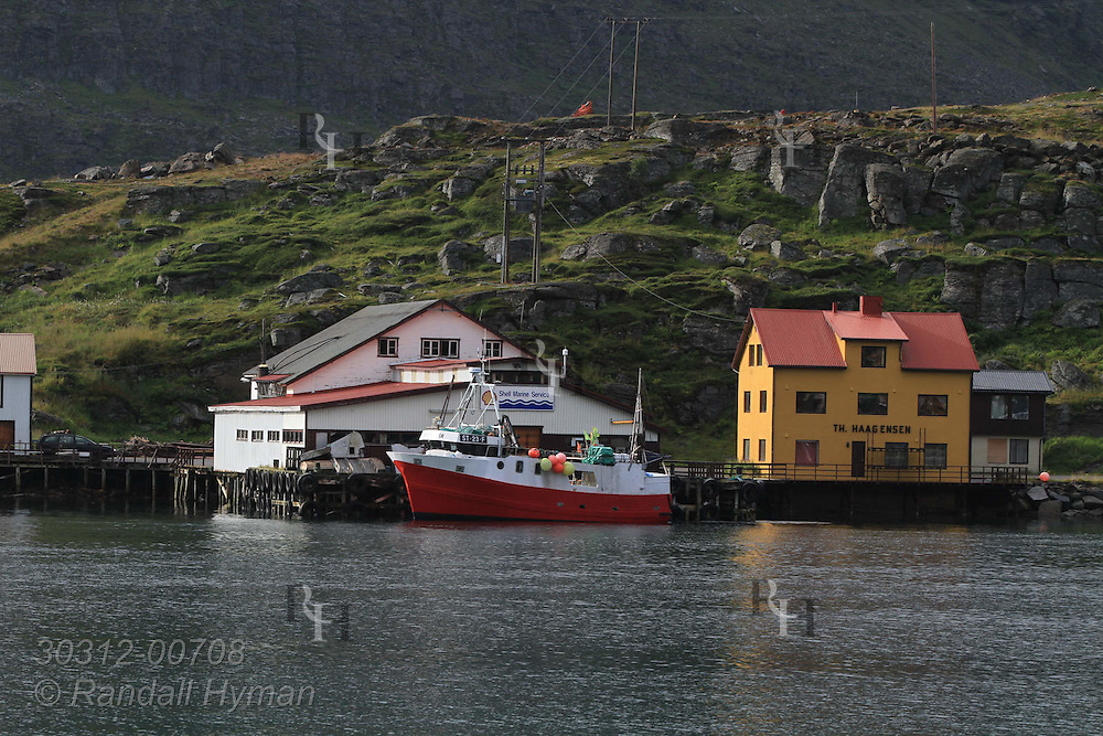 Wharf buildings line shore across from fishing village of Havoysund in Finnmark county, Norway.