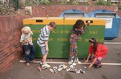 Multiracial group of young children recycling aluminium drinks cans,