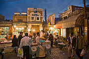 Vendors make brisk business at their market stalls as shoppers pick supplies for the next day at a souk in Sanaa, the capital of Yemen.