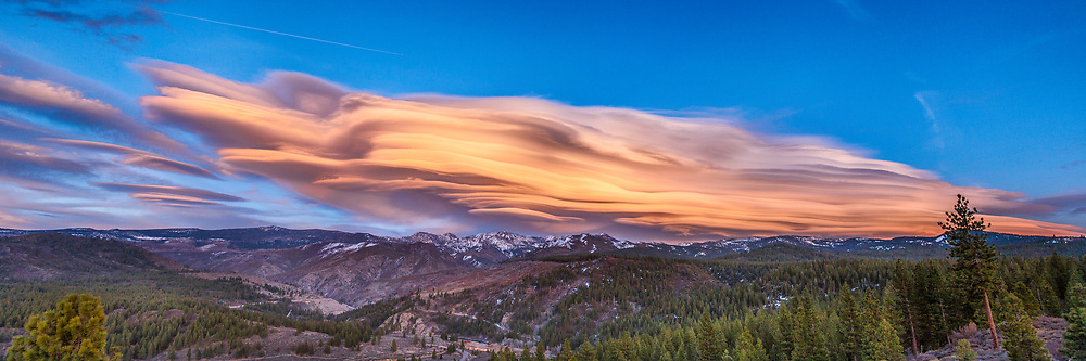 A panorama photo of a lenticular cloud above the Sierra Mountains in California