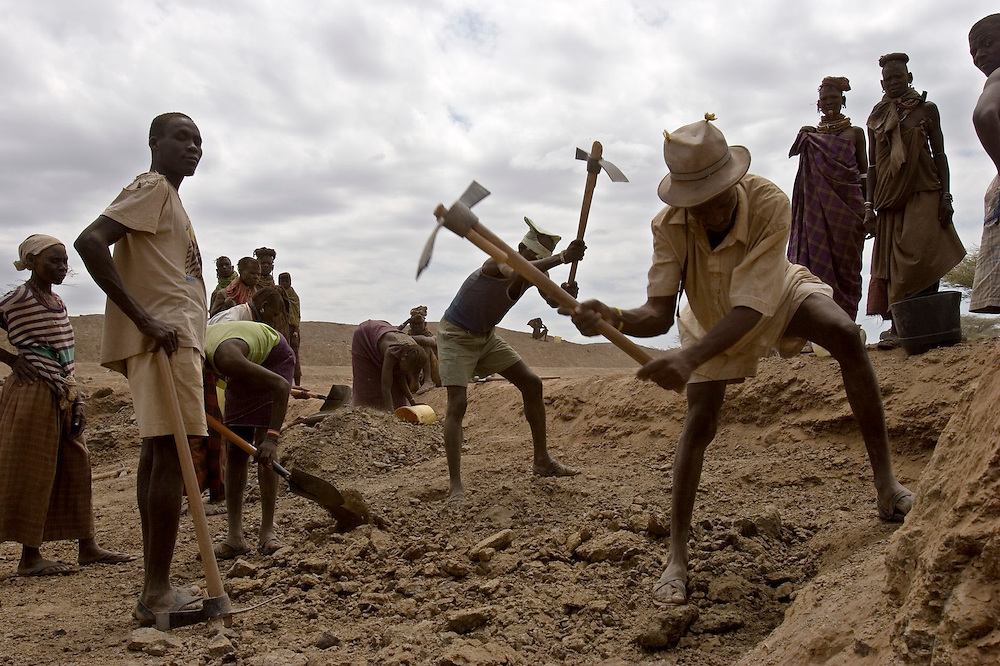 Local Turkana men & women from Kanukurudio dig a new water pan in Northern Kenya. The water pan rehabilitation project is organised by Oxfam and the local people are in a cash working scheme. 126 households in the surrounding area are employed for 5 months.