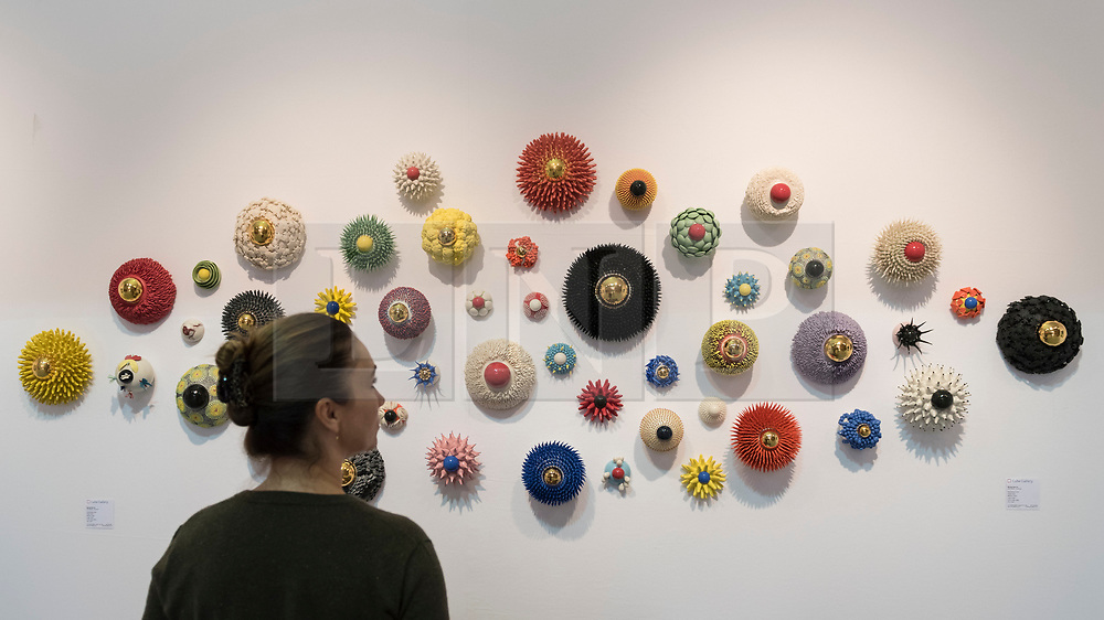 """© Licensed to London News Pictures. 20/06/2018. LONDON, UK. A visitor views """"Eye Series""""ceramics by Myung Nam An at The Art & Antiques Fair Olympia which runs 20 to 27 June at Kensington Olympia.  Photo credit: Stephen Chung/LNP"""