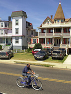 An unidentified man rides his bicycle in front of some of the Victorian homes on Beach Drive, Saturday, August 10, 2002, in Cape May, New Jersey. (Photo by William Thomas Cain/photodx.com)