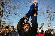 A man holds his baby, who was suffering from the effects of tear gas fired by Greek riot police at asylum seekers protesting in front of the Greek border crossing to Macedonia, over his head, shouting at police who had fired the gas. Several small children and babies were present when police fired tear gas into a group of protesters in an attempt to disperse the crowd on December 3, 2015. Dozens of asylum seekers, who had been stranded at the border for many days, camping out on railroad tracks and relying on aid from various international organizations,  forcfully barricaded the border on December 2. On November 17, 2015 Macedonia, Serbia, Slovenia and Croatia enacted border restrictions which blocked all asylum seekers, except those with documents proving they were from Syria, Iraq and Afhanistan, from entering any of those countries. Thousands of asylum seekers are currently stranded in Greece due to these restrictions.