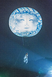 © Licensed to London News Pictures . 19/07/2013 . Suffolk , UK . A woman suspended from a moon balloon as Studio Festi perform Water Dance above a lake in Henham Park after sunset on the opening night of The Latitude music and culture festival in Henham Park , Southwold . Photo credit : Joel Goodman/LNP