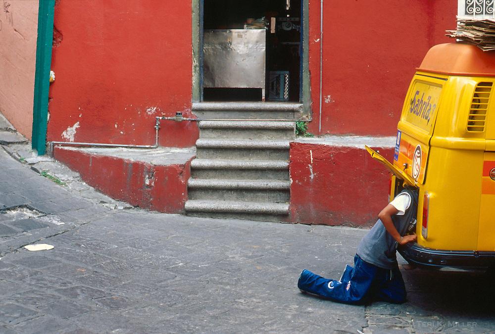 Boy works on his van, Guanajuato, Mexico.