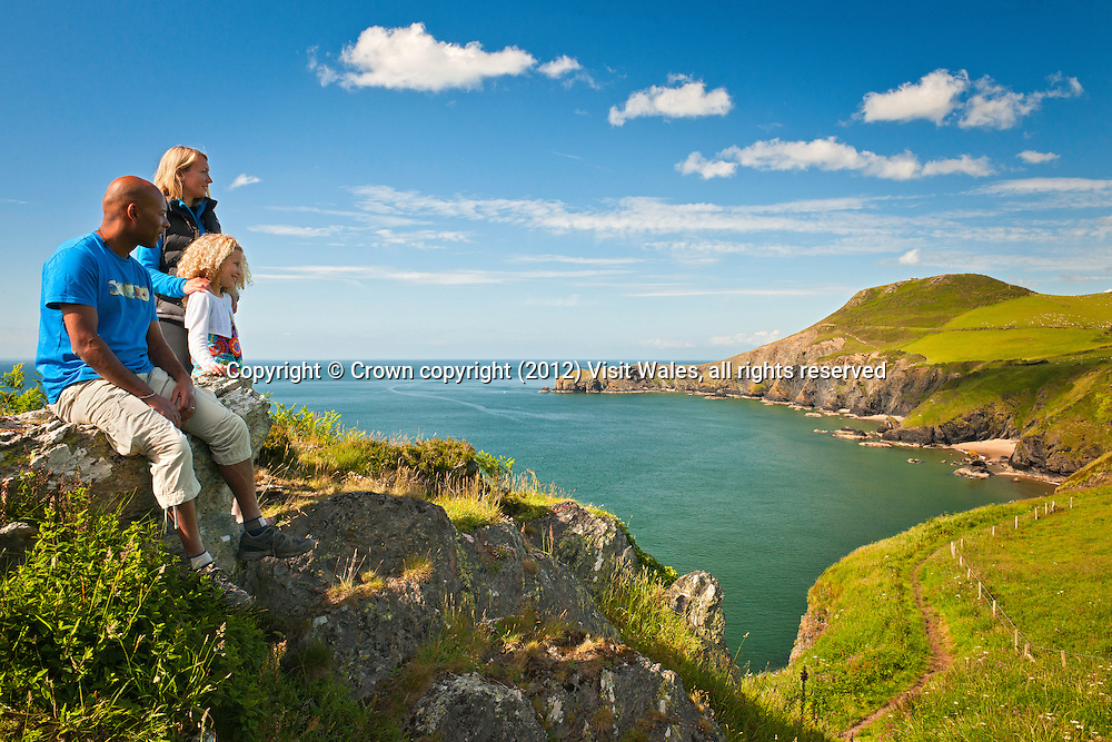 Mother, father and daughter resting on coast path<br /> Llangrannog<br /> Ceredigion<br /> Mid<br /> Walking<br /> Activities and Sports