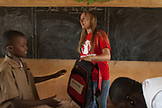 Save the Children staff Anne Civel (standing, center) hands a backpack with school materials to a student. <br /> Save the Children distributed education kits to students at Groupe Scolaire Quartier Lycée in Man, western Côte d'Ivoire. Children received a backpack with school supplies such as pens, pencils, sharpeners, notebooks, rulers, a pair of compasses and a portable chalkboard.