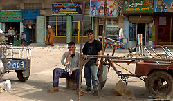 Two Iraqi young men sit beside an empty stall in front of a row of run down looking shops in a market area of Basra in March 2005