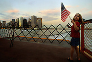 A young girl shows her patriotism as she and her family ride a ferry away from Manhattan as the smoke from the remains of the Twin Towers billow over the southern end of the island.