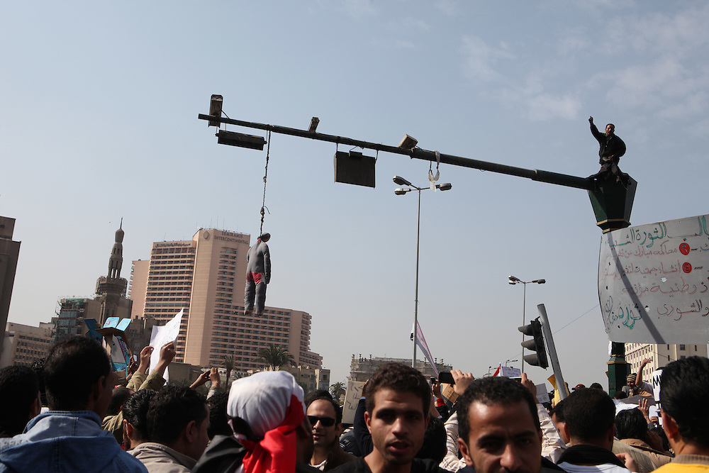 A protester stands atop a light post while an effigy of Hosni Mubarak hangs from it.