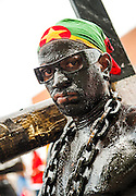 A man covered in oil and draped with large chains carries a wooden cross (crucifix) during the Caribbean Festival in Washington D.C.