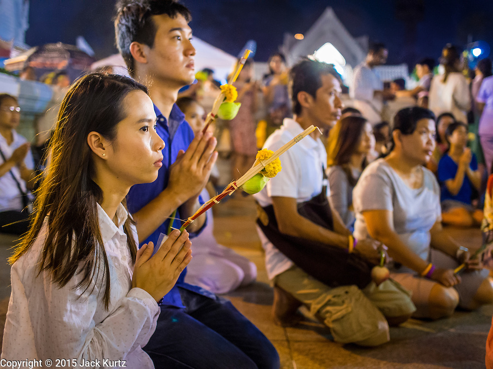 """04 MARCH 2015 - BANGKOK, THAILAND: People pray in front of the """"wiharn,"""" or prayer hall, at Wat Benchamabophit on Makha Bucha Day. Makha Bucha Day is an important Buddhist holy day and public holiday in Thailand, Cambodia, Laos, and Myanmar. Many people go to temples to perform merit-making activities on Makha Bucha Day. Wat Benchamabophit is one of the most popular Buddhist temples in Bangkok.    PHOTO BY JACK KURTZ"""