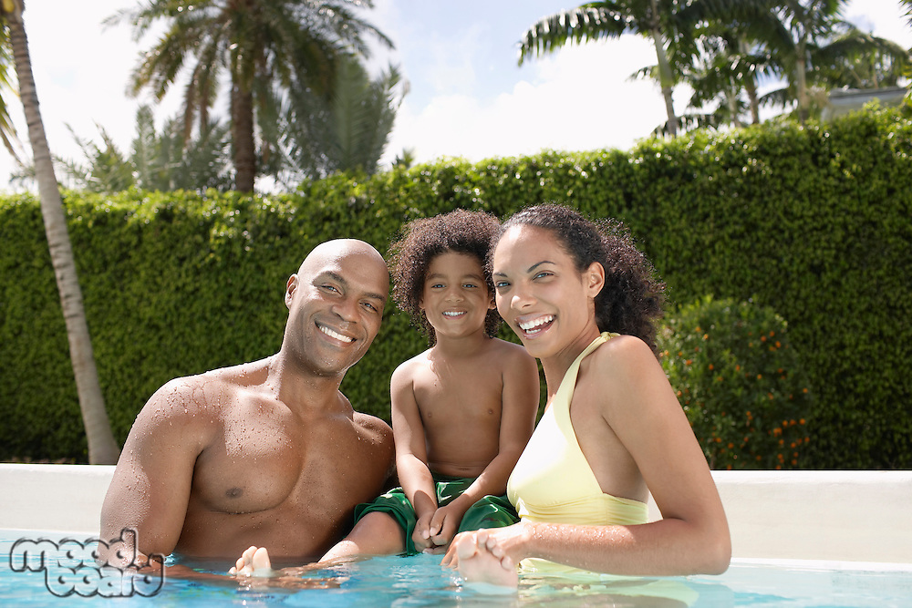 Parents with son (5-6 tears) in pool portrait