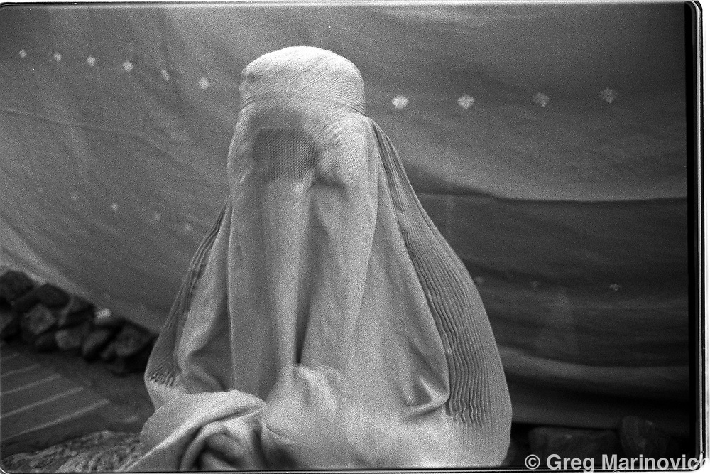 Women wear the burqa as they pass along the Panshir valley.  Women have to be covered at all times, even in areas controlled by the more lenient Northern Alliance, but in Taliban areas, they tempt death to show the slightest deviance from repressive tribal interpretation of Islam. Here, a female refugee in an area wear she is further secluded by blankets and material erected around a family area. (Greg Marinovich)
