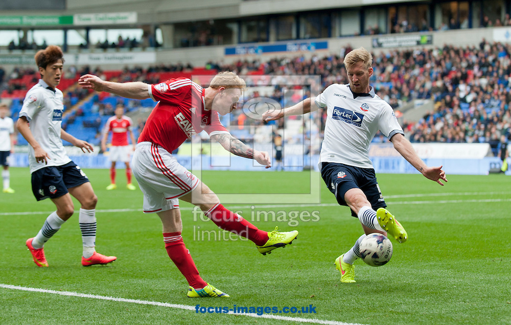 Tim Ream of Bolton Wanderers blocks a cross by Chris Burke of Nottingham Forest during the Sky Bet Championship match at the Macron Stadium, Bolton<br /> Picture by Russell Hart/Focus Images Ltd 07791 688 420<br /> 16/08/2014