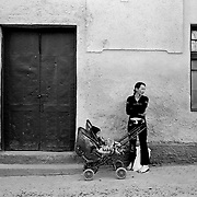 A Lady with a young boy in a pram wait in the high street of the small town of Rupea in the heart of Transylvania, Romania. Photo Tim Clayton..Romania entered the European Economic Community in January 2007, signaling a fresh exodus of the work force as many Romanians fled the country in search of a better life. Sadly many have not found the employment sought and Romanian communities camped in European cities are making headlines for all the wrong reasons...In a nation recovering from communist rule from 1947 to 1989 and a decade of economic instability and decline that followed, it is estimated Romania has lost between 2.0 and 2.5 million of it's workforce since the end of communist rule. Considering Romanian's population is estimated at 22 million, this is about 10% of the Country's population...Life goes on as normal for those who have remained in Romania. In a country steeped in history and culture there has been little or no change in age old traditions, life is personified in the rural communities where a third of Romanian's population is employed in agriculture and primary production, one of the highest in Europe.