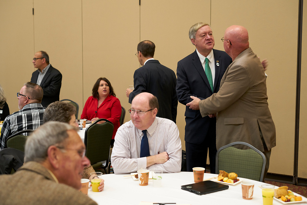 President Nellis greets faculty members at his first Breakfast for Progress.