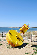 Yellow channel marker on the beach at Wellfleet harbor, Cape Cod Massachusetts
