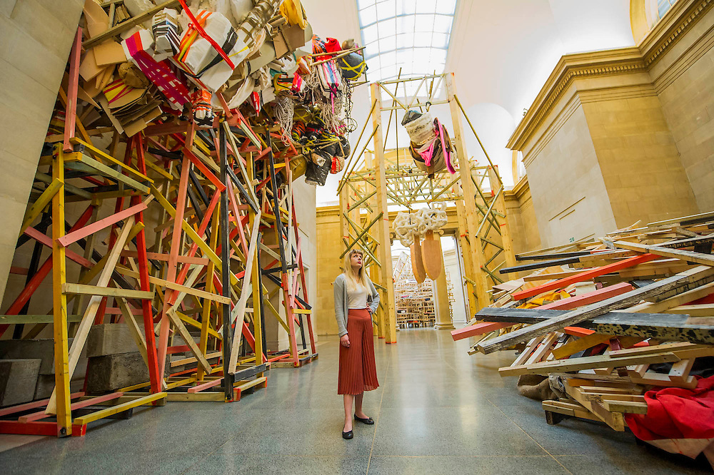 Phyllida Barlow's new work 'dock' is the new installation, which fills Tate Britain's Duveen Galleries. Here untitled:dock:hungcowledtubes and 5stockadecrates and crashed/lintel/brokensculpture/paintedtarps. It has been created as part of the annual Tate Britain Commission, in which a leading contemporary artist is invited to develop a work inspired by Tate's Collection. Phyllida Barlow has worked for over four decades with inexpensive, everyday materials to create large sculptural installations and bold and colourful three-dimensional collages. Tate Britain, Millbank, London, UK 31 March 2014.   Guy Bell Photography, 07771 786236, guy@gbphotos.com