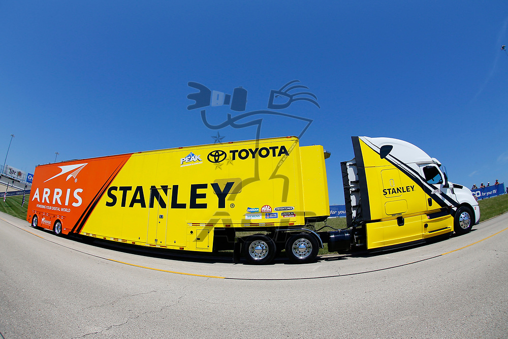 The hauler for Daniel Suarez (19) drives through the infield during hauler parking for the Overton's 400 at Chicagoland Speedway in Joliet, Illinois .