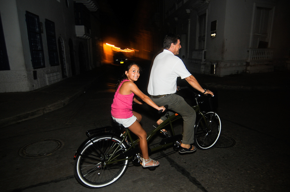 A young girl and her father ride through Cartagena, Colombia on a tandem bicycle.