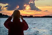 Nederland, Millingen, 13-7-2016Passagier van een pont, veerpont, over de Waal, Rijn, maakt een foto van de mooie rode en oranje lucht van een zonsondergang .Foto: Flip Franssen
