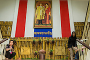 "01 FEBRUARY 2014 - BANGKOK, THAILAND:  Election workers hide from voters under a portrait of Bhumibol Adulyadej, the King of Thailand, and his wife Queen Sirikit while protesting voters try to get into the polling place in Din Daeng. Thais went to the polls in a ""snap election"" Sunday called in December after Prime Minister Yingluck Shinawatra dissolved the parliament in the face of large anti-government protests in Bangkok. The anti-government opposition, led by the People's Democratic Reform Committee (PDRC), called for a boycott of the election and threatened to disrupt voting. Many polling places in Bangkok were closed by protestors who blocked access to the polls or distribution of ballots. The result of the election are likely to be contested in the Thai Constitutional Court and may be invalidated because there won't be quorum in the Thai parliament.   PHOTO BY JACK KURTZ"