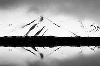 Snow melting on the dark rocks of Spitsbergen to form patterns, Svalbard.