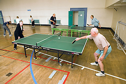 Group of older people playing table tennis in a sports hall,
