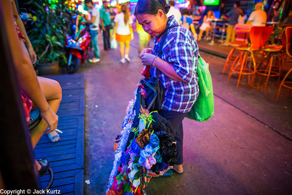 "12 JANUARY 2013 - BANGKOK, THAILAND:  A woman who sells garters to entertainers in Soi Cowboy red light district show her products to ""ladyboy"" (transgendered) entertainers on the Soi. In Thai, the ladyboys are called kathoey. Many work in the entertainment and night life sectors of the Thai economy. Prostitution in Thailand is illegal, although in practice it is tolerated and partly regulated. Prostitution is practiced openly throughout the country. The number of prostitutes is difficult to determine, estimates vary widely. Since the Vietnam War, Thailand has gained international notoriety among travelers from many countries as a sex tourism destination. One estimate published in 2003 placed the trade at US$ 4.3 billion per year or about three percent of the Thai economy. It has been suggested that at least 10% of tourist dollars may be spent on the sex trade. According to a 2001 report by the World Health Organisation: ""There are between 150,000 and 200,000 sex workers (in Thailand).""    PHOTO BY JACK KURTZ"
