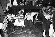 A group of Punks sat down at a gig, UK, 1980's.
