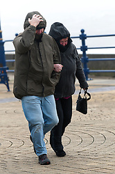 © Licensed to London News Pictures. 8/02/2016. Porthcawl, Bridgend, Wales, UK. A man and woman brave the wind on the seafront. People struggle to stay on their feet in winds gusting over approximately 60mph. Storm Imogen batters the small Welsh seaside resort of Porthcawl in the county borough of Bridgend on the South coast of Wales, UK. Photo credit: Graham M. Lawrence/LNP