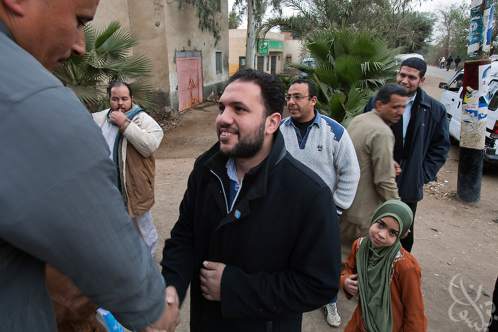 Mohamed Abbas, an Egyptian Revolutionary Council member and Parliamentary candidate shakes hands of area residents near Benha, Egypt January 18, 2012. Abbas, split from the Muslim Brotherhood to campaign for a new party he feels will better represent young Egyptians like himself.