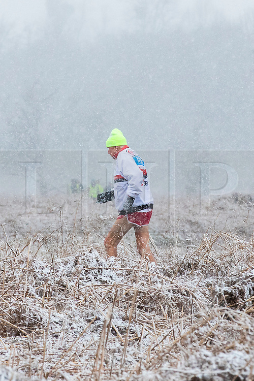 © Licensed to London News Pictures. 17/03/2018. London, UK. A runner braves cold weather in Bushy Park as more snow falls over London. Photo credit: Rob Pinney/LNP