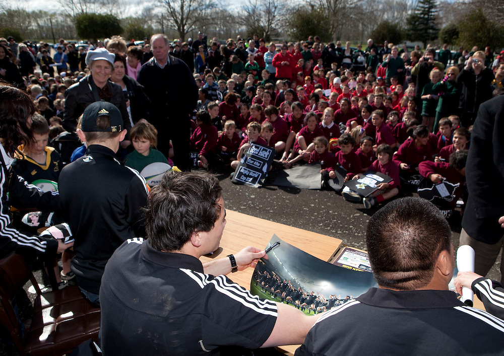 All Blacks Zac Guildford and Kevin Mealamu sign posters at Russell Park, Waipukarau for a visit promoting the rugby world cup, Waipukarau, New Zealand, Friday September 02, 2011. Photo: SNPA / John Cowpland