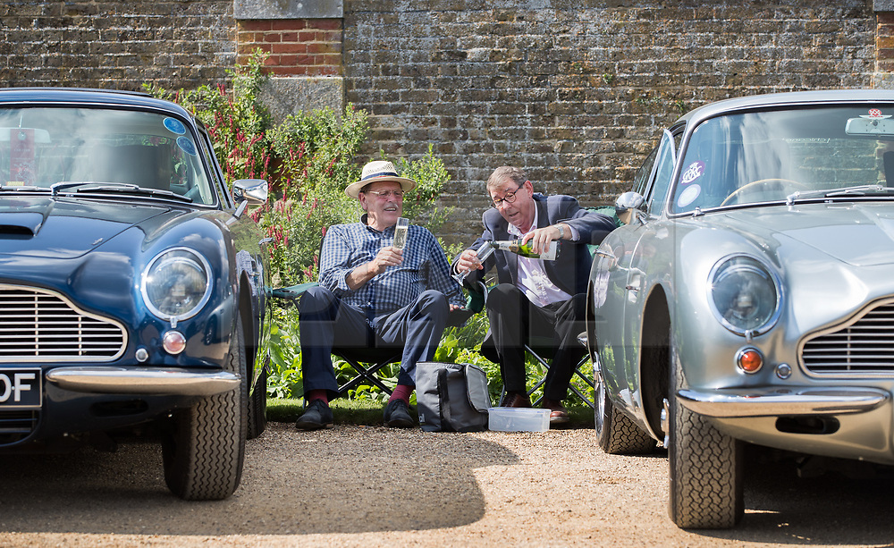 © Licensed to London News Pictures. 02/09/2017. London, UK. Two Aston Martin owners enjoy a drink at the Concours of Elegance show in the grounds of Hampton Court Palace. The Concours of Elegance brings together, over three days, a selection of 60 of the rarest cars from around the world some of which have never been seen before in the UK. Each car owner is asked to vote on the other models on display to decide which car is considered to be the 'Best of Show'. The show also displays of hundreds of other fine motor cars, including entrants to The Club Trophy. Photo credit: Peter Macdiarmid/LNP