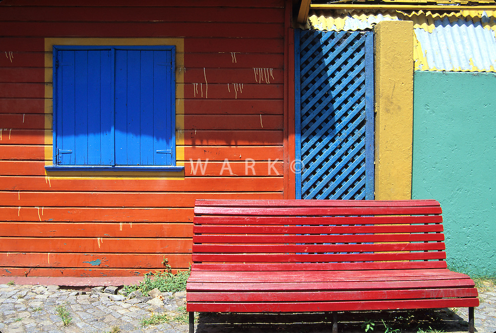 red bench by colorful wall. Buenos Aires, Argentina. 1994