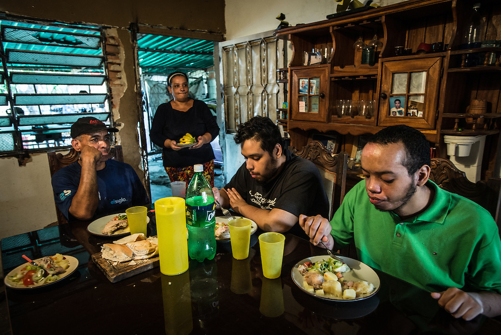 MARACAY, VENEZUELA - JULY 4, 2016: Mario Simeone and Evelin RodrÍguez eat lunch with their two schizophrenic sons, Gerardo (right) and Accel (second from right).  The economic crisis that has left Venezuela with little hard currency has already hit its health system, leaving hospitals without antibiotics, surgeons without gloves and patients dying on emergency room tables.  But beyond the hospital wards, thousands more mental health patients—many of whom had been living relatively normal lives at home with their families under medication—are slipping back into relapse for lack of basic psychiatric medications which control their symptoms, medical experts say. PHOTO: Meridith Kohut for The New York Times
