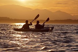United States, Washington, Seattle.  A couple paddles a two-person sea kayak in Elliott Bay at sunset, looking west to the Olympic Mountains.