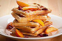 waffles stacked with fresh fruit topping on white plate on wooden table