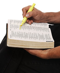 close-up of man holding open Bible on knee, hilighting verses