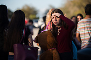"Marjory Stoneman Douglas High School student Dalila Ladero, 16, of Coral Springs, stands near friends after being reunited with her mother hours after a mass-casualty shooting at the school Tuesday, Feb. 14, 2018, in Parkland. ""When all that happened, I wasn't in my class, I just started following people...I was just seeing everyone screaming and crying and I didn't know what was happening,"" the student at the school said. ""I was calm, I just started praying."" (XAVIER MASCAREÑAS/TREASURE COAST NEWSPAPERS)"