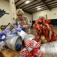 Teresa Gholston helps hang ornamnets this week as volunteers get the Tupelo Furniture Market Building V ready for next week's annual Celebration Village.