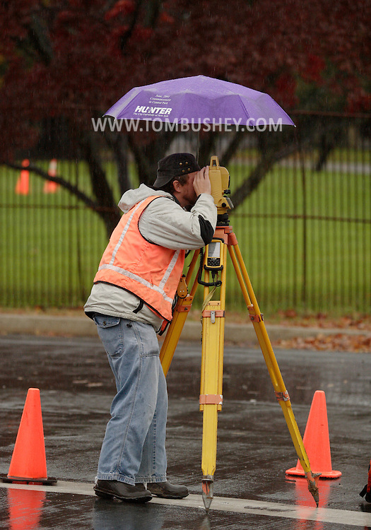 Middletown, NY - A surveyor uses an umbrella to stay dry while working on rainy day on Nov. 15, 2007.