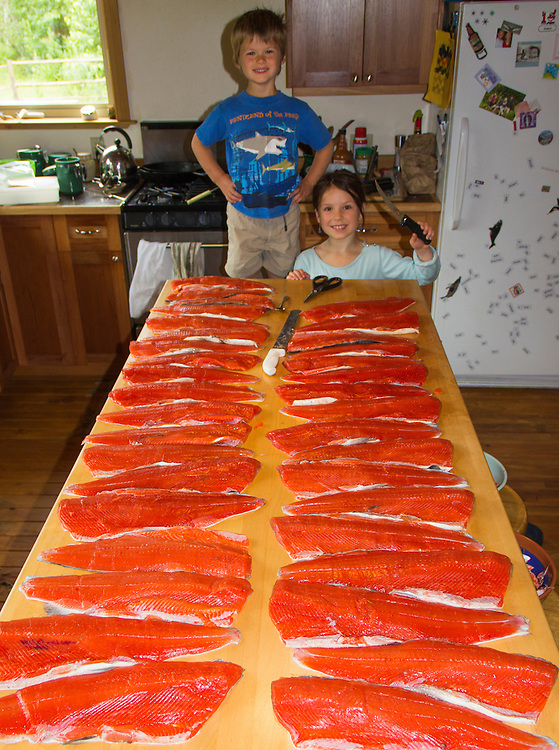 A young boy and girl look over the processing of many sockeye salmon. MR