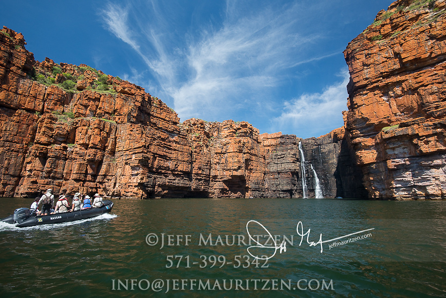 Expedition travelers aboard a zodiac inflatable boat explores the King George River and waterfall in the Kimberley Region of Western Australia.
